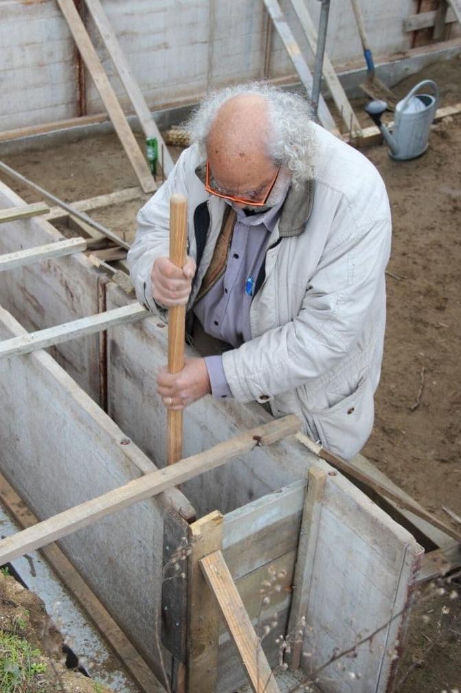 Paul Casanova architecte devant un mur en terre crue banchée