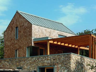 Couverture et détails architecturaux en zinc pour souligner l'harmonie de matériaux naturels d'une maison familiale Batiweb