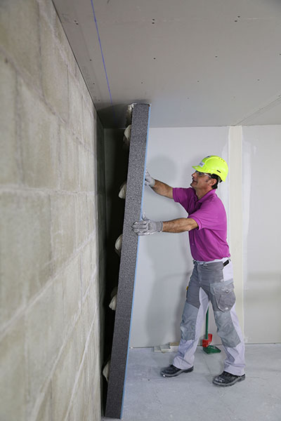 Mise en œuvre du doublage collé PRÉGYMAX 13 + 120 améliorant l'isolation acoustique et thermique des murs.